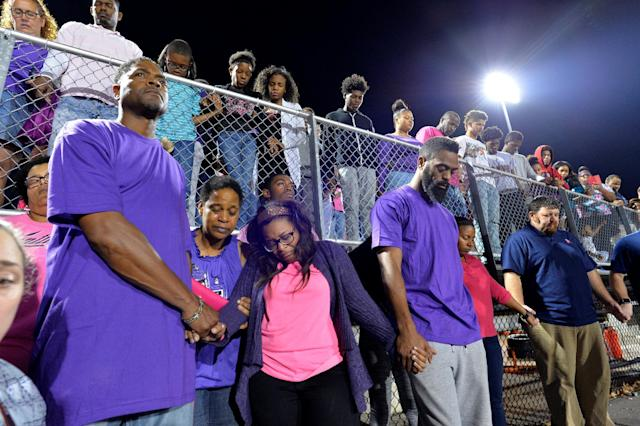 Shoshana Boyd (center L) and Olympic sprinter Tyson Gay (center R) stand surrounded by those gathered during a candlelight vigil at Lafayette High School for their daughter Trinity Gay, who died in an exchange of gunfire early Sunday morning, in Lexington, Kentucky, October 17, 2016. REUTERS/Bryan Woolston