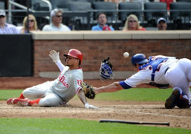 Philadelphia Phillies' Freddy Galvis (13) scores safely at home plate on a single by Jimmy Rollins as New York Mets catcher Anthony Recker (20) bobbles the ball in the seventh inning of a baseball game on Sunday, Aug. 31 2014, in New York. (AP Photo/Kathy Kmonicek)