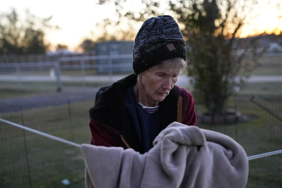 Lou Ann Trahan, who suffers from dementia, takes a blanket off a clothes line to stay warm on Christmas Eve, in the gutted home of her daughter in the aftermath of Hurricane Laura and Hurricane Delta, in Lake Charles, La., Thursday, Dec. 24, 2020. The extended family is living in tents and campers on the property, having all lost their homes to the storms. (AP Photo/Gerald Herbert)
