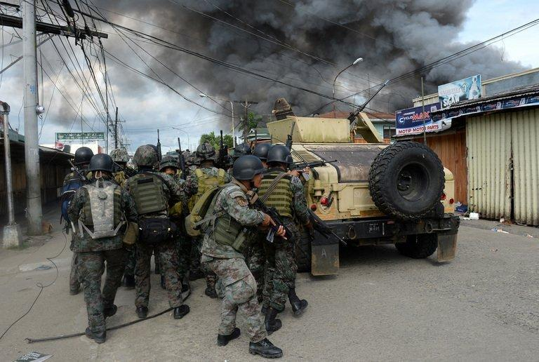 Philippines forces take cover during a fire fight with Muslim rebels in Zamboanga on September 12, 2013. At least 22 people have been killed and 52 wounded in five days of fighting, while 19 of the gunmen have surrendered or been captured