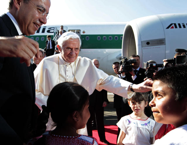 Mexico's President Felipe Calderon, left, looks on as Pope Benedict XVI is greeted by children at the airport in Silao, Mexico, Friday March 23, 2012. Benedict's weeklong trip to Mexico and Cuba is his first to both countries. (AP Photo/Gregorio Borgia)