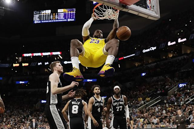 Los Angeles Lakers forward LeBron James (23) hangs on the rim as he scores against the San Antonio Spurs during the first half of an NBA basketball game, in San Antonio, Monday, Nov. 25, 2019. (AP Photo/Eric Gay)