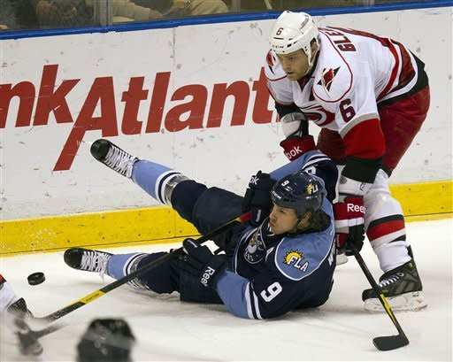 Florida Panthers' Stephen Weiss (9) and Carolina Hurricanes' Tim Gleason (6) battle for the puck during the first period of an NHL hockey game in Sunrise, Fla., Sunday, March 11, 2012. (AP Photo/J Pat Carter)