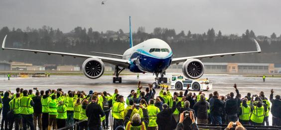 Boeing employees and family members cheer the 777X after it landed at Boeing Field in Seattle (AP)