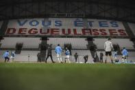 "Marseille players warm up as a tribune decorated by their fans directed at team reads ""You disgust us"" ahead of the French League One soccer match between Marseille and Lens at the Veledrome stadium in Marseille, France, Wednesday, Jan. 20, 2021. (AP Photo/Daniel Cole)"