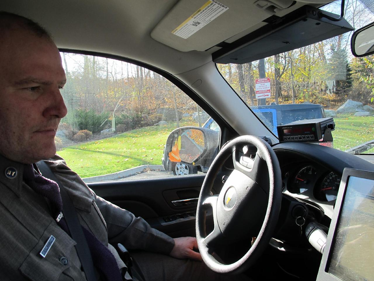 New York State Trooper Clayton Howell checks a screen that displays driving records inside his patrol vehicle in Hawthorne, N.Y., on Thursday, Nov. 14, 2013. Troopers are using a fleet of tall, unmarked SUVs as part of a crackdown on texting while driving. (AP Photo/Jim Fitzgerald)