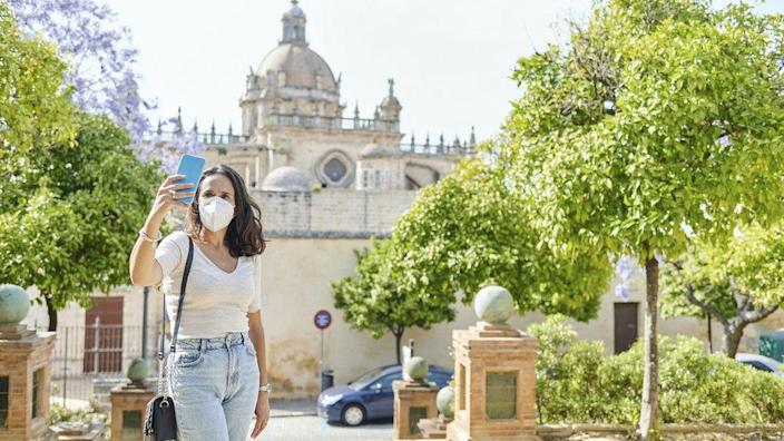 A woman wearing an N95 mask poses for a selfie next to a tourist attraction in Spain