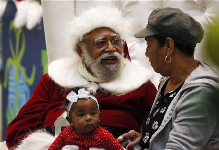 African American Santa Claus Langston Patterson (L), 77, poses with four-month-old Raelyn Price and her grandmother Gloria Boissiere, at Baldwin Hills Crenshaw Plaza mall in Los Angeles, California, December 16, 2013. REUTERS/Lucy Nicholson