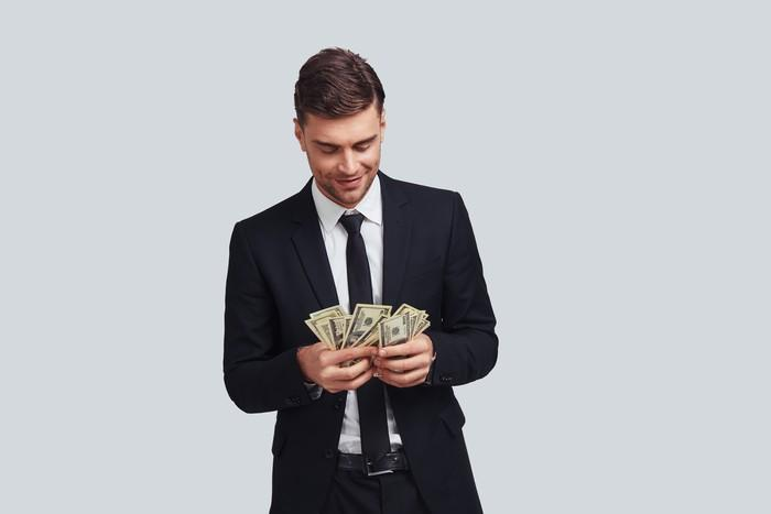 Wealthy young man in suit counting money.