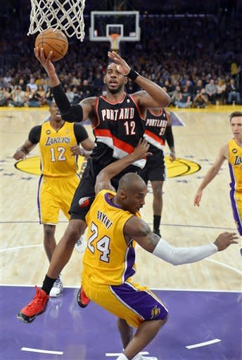 Portland Trail Blazers forward LaMarcus Aldridge, top, goes up for a shot as Los Angeles Lakers guard Kobe Bryant falls during the first half of their NBA basketball game, Friday, Feb. 22, 2013, in Los Angeles. (AP Photo/Mark J. Terrill)