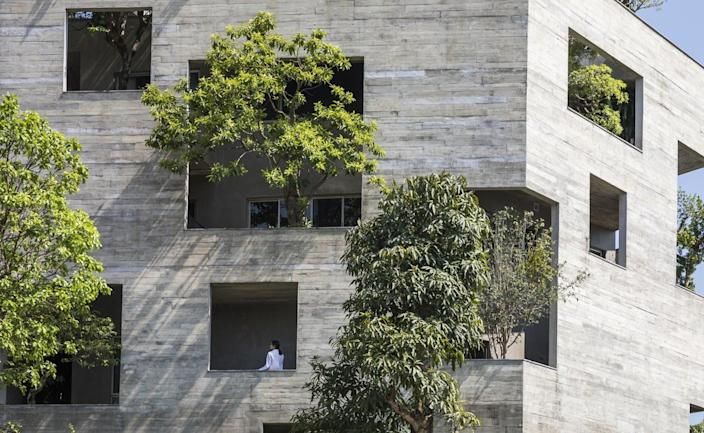 Large trees of all shades of green burst out from openings in the villa's exterior facade.