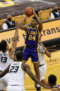 LSU's Cameron Thomas, top, shoots over Missouri's Mark Smith, left, and Jeremiah Tilmon, right, during the first half of an NCAA college basketball game Saturday, March 6, 2021, in Columbia, Mo. (AP Photo/L.G. Patterson)
