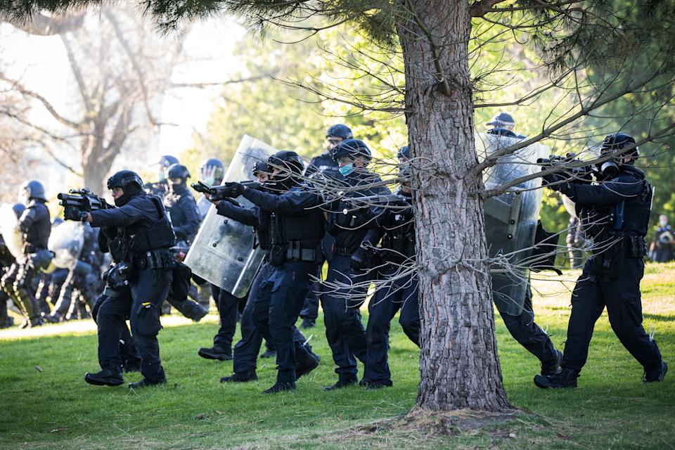 MELBOURNE, AUSTRALIA - SEPTEMBER 22: Members of the Critical Incident Response Team (CIRT) with Victoria Police move in and fire non-lethal crowd control rounds at protesters refusing to leave the Shrine of Remembrance on September 22, 2021 in Melbourne, Australia. Protests started on Monday over new COVID-19 vaccine requirements for construction workers but  turned into larger and at times violent demonstrations against lockdown restrictions in general. Melbourne is currently subject to COVID-19 lockdown restrictions, with people only permitted to leave home for essential reasons. (Photo by Darrian Traynor/Getty Images)