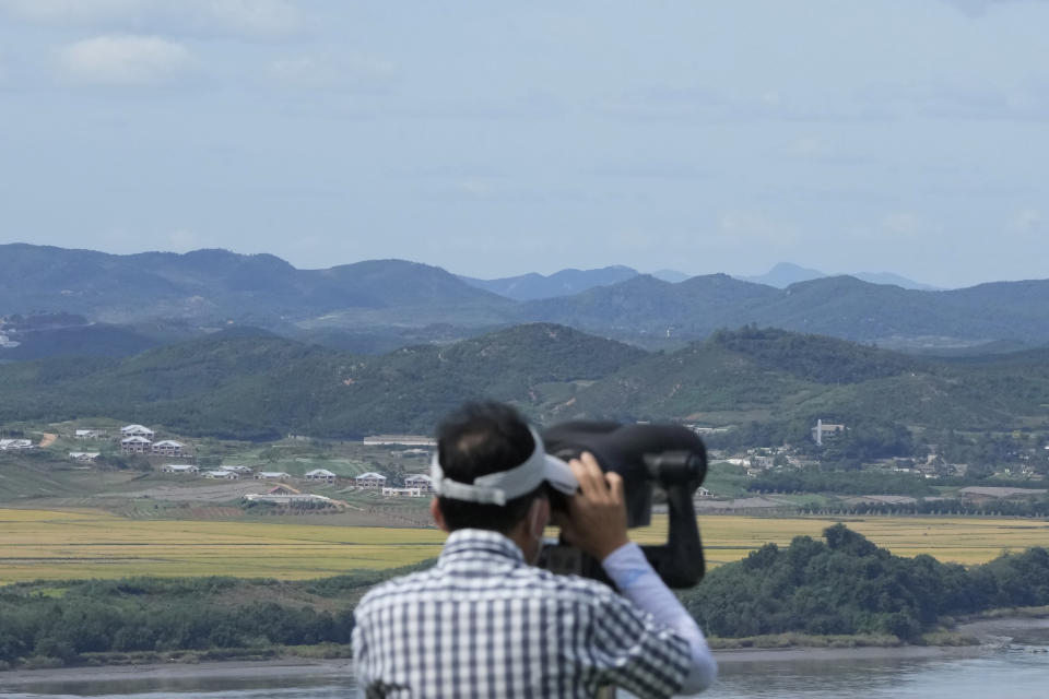 A visitor watches the North Korea side from the Unification Observation Post in Paju, South Korea, near the border with North Korea, Sunday, Sept. 26, 2021. The powerful sister of North Korean leader Kim Jong Un said Saturday that her country will take steps to repair ties with South Korea, and may even discuss another summit between their leaders, if the South drops what she described as hostility and double standards. (AP Photo/Ahn Young-joon)