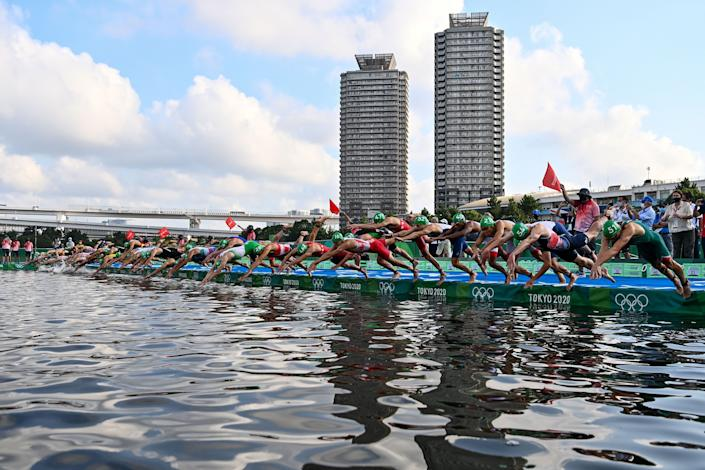 <p>Athletes compete in the men's individual triathlon competition during the Tokyo 2020 Olympic Games at the Odaiba Marine Park in Tokyo on July 26, 2021. (Photo by Loic VENANCE / AFP) (Photo by LOIC VENANCE/AFP via Getty Images)</p>