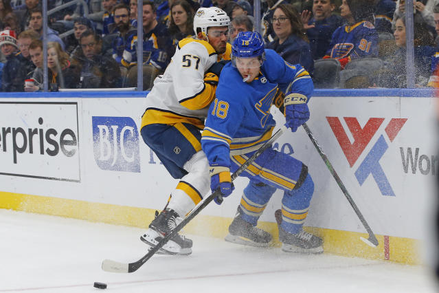 St. Louis Blues' Robert Thomas, right, is checked off the puck by Nashville Predators' Dante Fabbro during the second period of an NHL hockey game Saturday, Feb. 15, 2020, in St. Louis. (AP Photo/Billy Hurst)