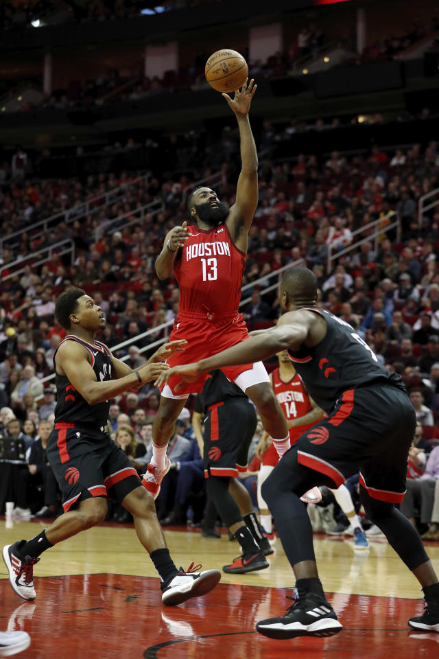 HOUSTON, TX - JANUARY 25: James Harden #13 of the Houston Rockets goes up for a shot defended by Kyle Lowry #7 of the Toronto Raptors and Serge Ibaka #9 in the first half at Toyota Center on January 25, 2019 in Houston, Texas. (Photo by Tim Warner/Getty Images)
