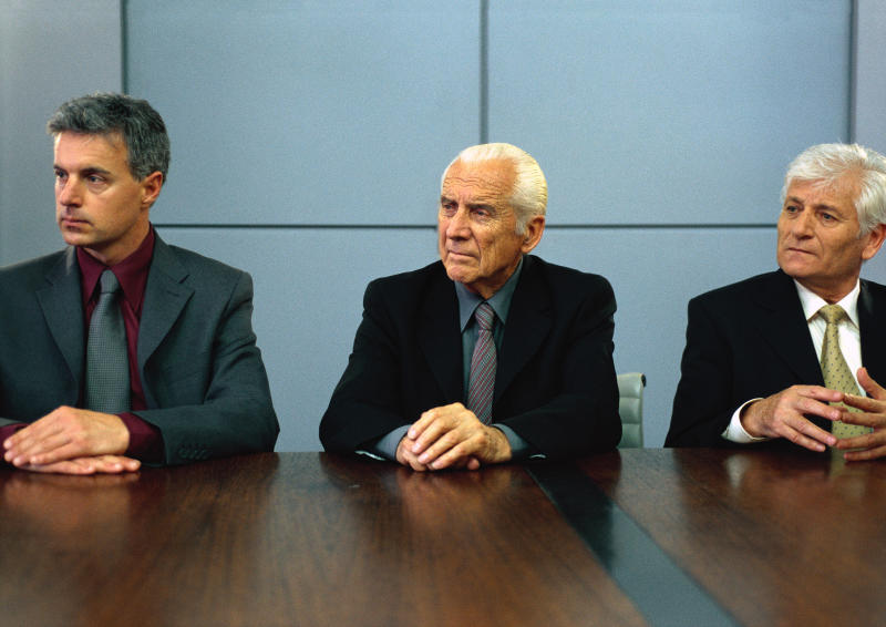 Three businessmen sitting at conference table with hands on table, portrait