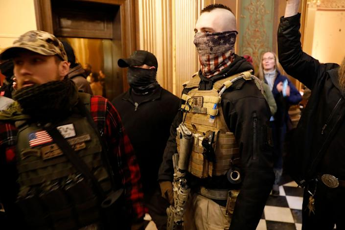 A protester bearing a weapon and dressed in a bulletproof vest tries to enter the Michigan State Capitol