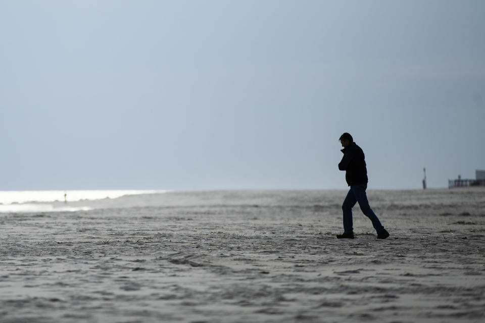 FILE - In this March 18, 2020, file photo, a person walks toward the ocean in Cape May, N.J. As the weather warms, some already have begun venturing outside, despite guidance to stay home. Government officials say they aim to manage public health risks in a way that allows for a gradual return to normal, but with the course of the outbreak still unknown, nobody is sure what summer will bring. (AP Photo/Matt Rourke, File)