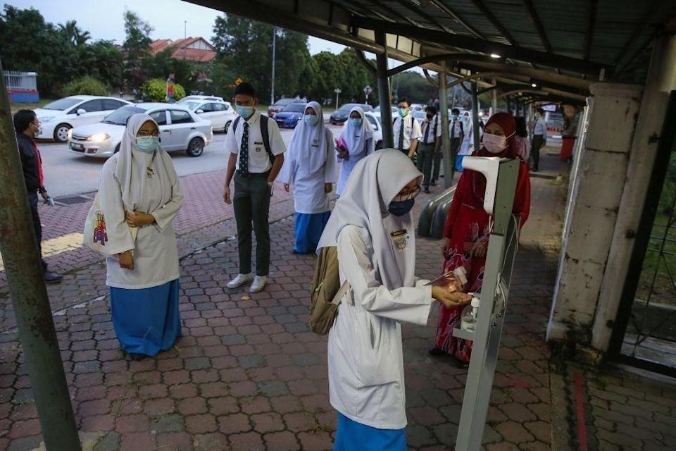 A student sanitises her hands after having her temperature recorded at Sekolah Menengah Kebangsaan Bukit Jelutong in Shah Alam January 20, 2021. — Picture by Yusof Mat Isa