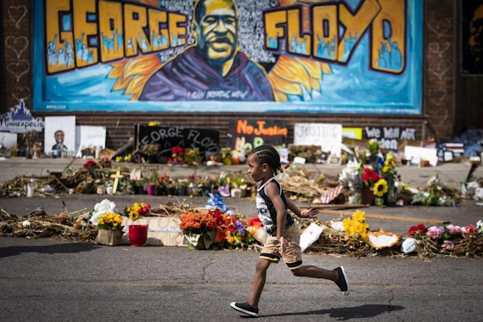 """<span class=""""element-image__caption"""">A child runs past a mural at the George Floyd memorial outside Cup Foods in Minneapolis.</span> <span class=""""element-image__credit"""">Photograph: Leila Navidi/AP</span>"""