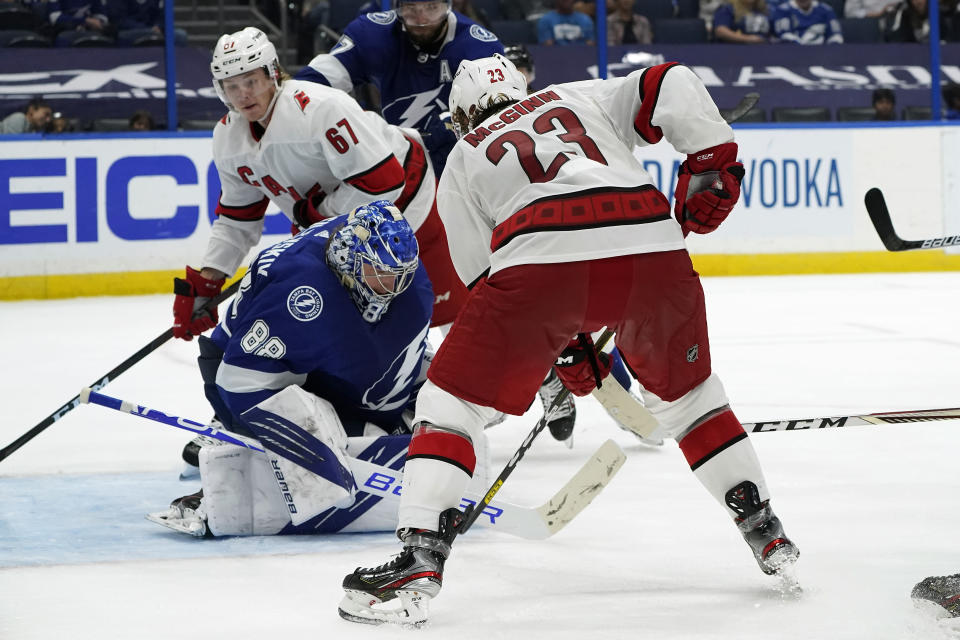 Tampa Bay Lightning goaltender Andrei Vasilevskiy (88)makes a save as Carolina Hurricanes left wing Brock McGinn (23) and center Morgan Geekie (67) look for a rebound during the third period in Game 4 of an NHL hockey Stanley Cup second-round playoff series Saturday, June 5, 2021, in Tampa, Fla. (AP Photo/Chris O'Meara)