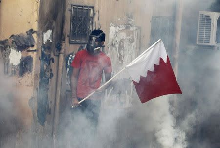 A protester is seen with a Bahraini flag as tear gas clouds surround him during clashes in the village of Bilad Al Qadeem