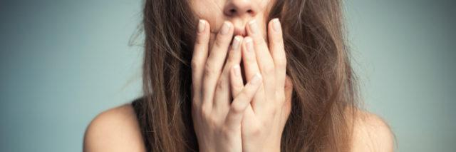 close up photo of woman with long hair and hands raised to her mouth in shock or panic