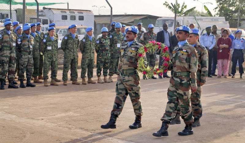 In this photo released by the United Nations Mission in South Sudan (UNMISS), U.N. peacekeepers walk to lay flowers on coffins of their two colleagues who were killed on Thursday, at a memorial service held in the UNMISS compound in Juba, South Sudan, Saturday, Dec. 21, 2013. The U.N. peacekeeping mission strongly condemned the unprovoked attack on a U.N. base in Akobo in Jonglei state, near the Ethiopian border, on Thursday that killed two Indian peacekeepers and injured a third. (AP Photo/UNMISS)