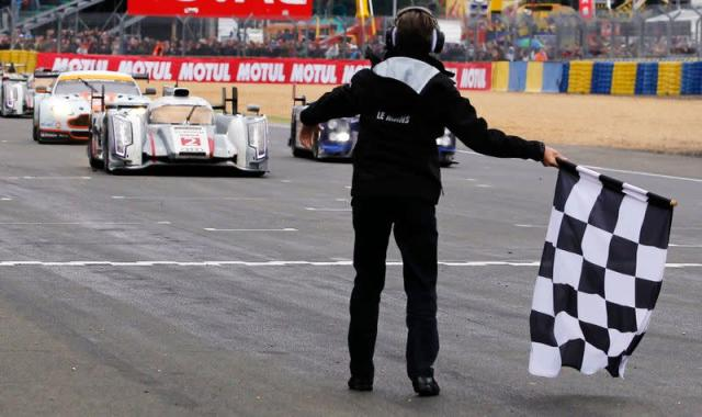 Denmark's Kristensen, driving the Audi R18 E-Tron Quattro Number 2, crosses the finish line at the Le Mans 24-hour sportscar race in Le Mans