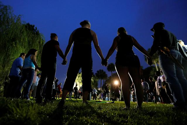 <p>People hold hands in a circle during a vigil in a park in Orlando, Fla., June 12, 2016. (Carlo Allegri/Reuters) </p>
