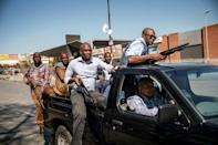 Plainclothes police patrol the Johannesburg township of Alexandra after the unrest