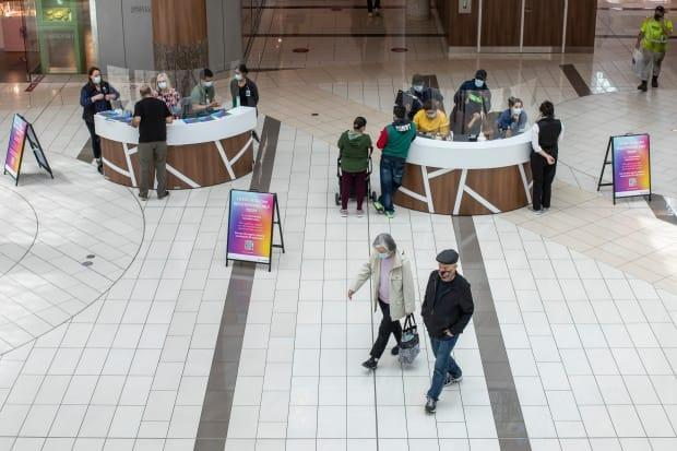 People are pictured at a Fraser Health COVID-19 registration kiosk at Guildford Mall in Surrey, B.C., on May 6.  (Ben Nelms/CBC - image credit)