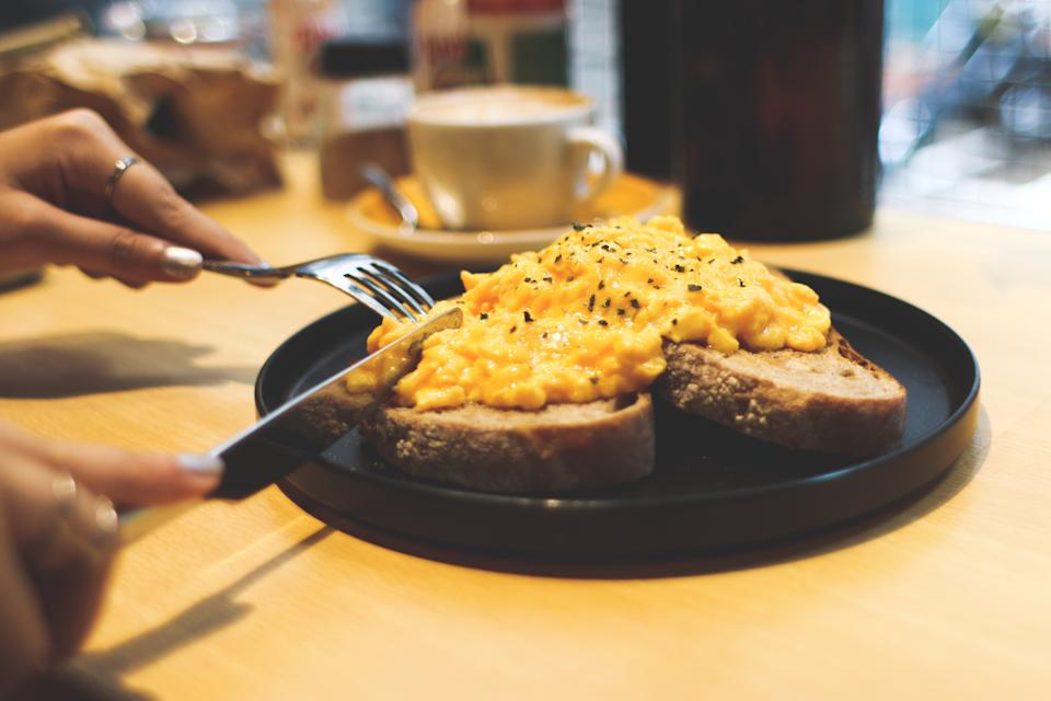 A woman eating scrambled eggs on toast.