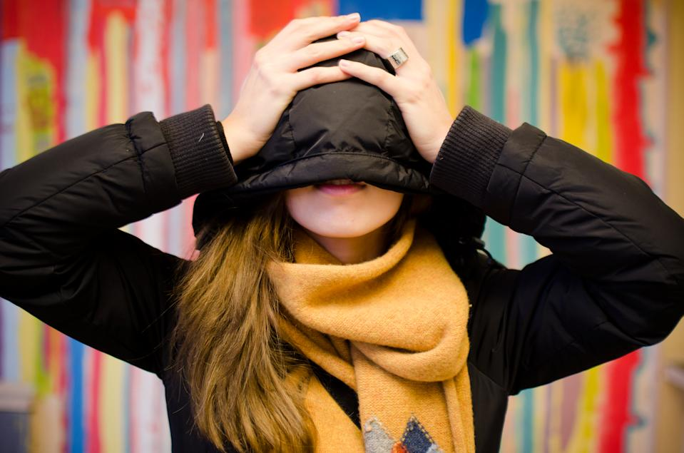 Beautiful young woman hiding face behind hoodie. In black jacket with scarf.
