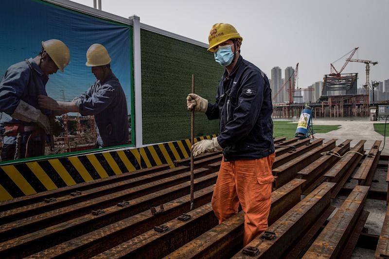 An employee wearing a face mask works at a construction site of a bridge in Wuhan in China's central Hubei province on March 24, 2020. - China announced on March 24 that a lockdown would be lifted on more than 50 million people in central Hubei province where the coronavirus first emerged late last year. (Photo by STR / AFP) / China OUT (Photo by STR/AFP via Getty Images)