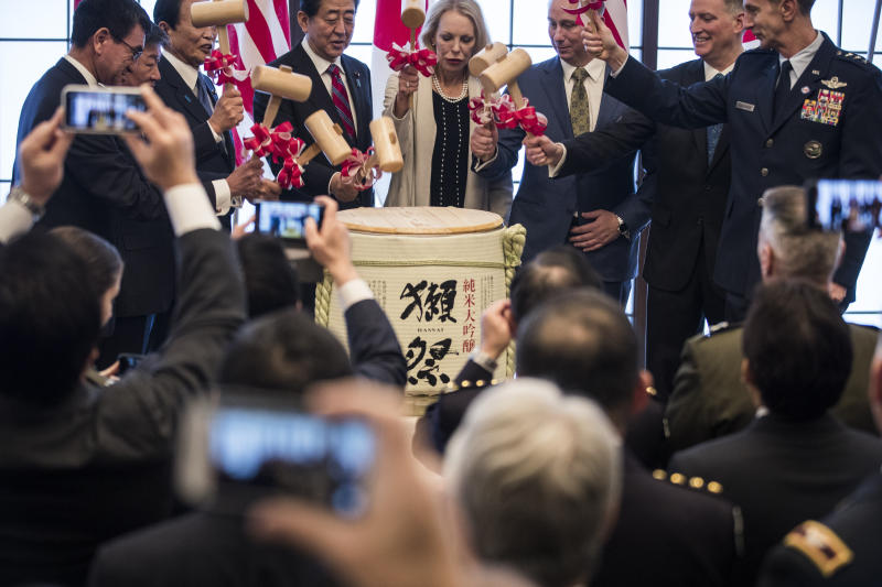 From left;  Japan's Defense Minister Taro Kono, Foreign Minister Toshimitsu Motegi, deputy prime minister Taro Aso, Prime Minister Shinzo Abe, granddaughter Mary Jean Eisenhower and the great grandson Merrill Eisenhower Atwater of former U.S. President Dwight Eisenhower, acting U.S. Ambassador to Japan Joseph M. Young and Commander of the U.S. Forces in Japan Lieutenant General Kevin Schneider break a barrel of sake to celebrate the 60th anniversary commemorative reception of the signing of the Japan-US security treaty at the Iikura Guesthouse in Tokyo on Sunday, Jan. 19, 2020. (Behrouz Mehri/Pool Photo via AP)