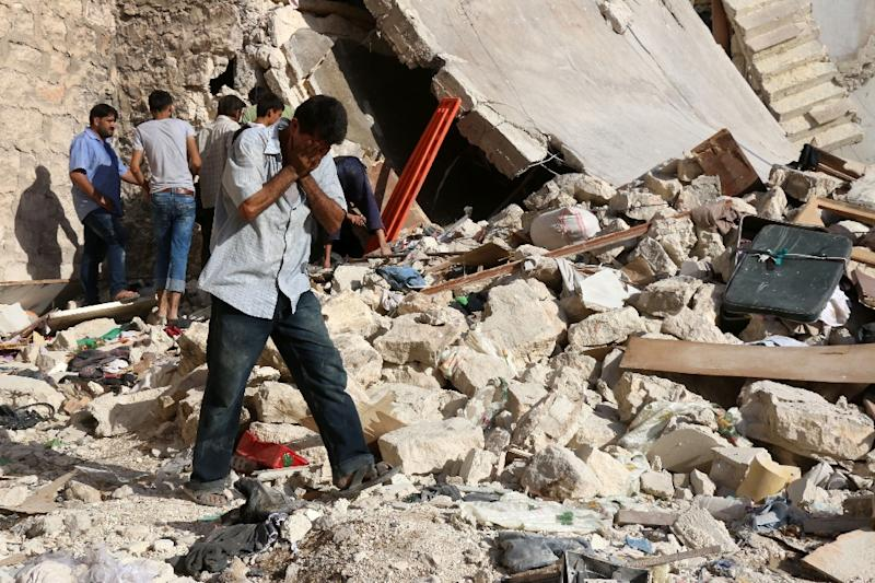 A Syrian man reacts as rescuers look for victims under the rubble of a collapsed building following a reported air strike in Aleppo on July 19, 2016