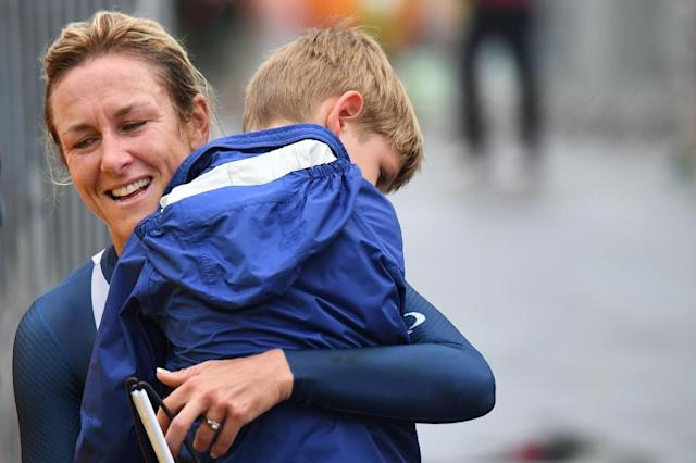 Kristin Armstrong celebrates with her son after winning the women's individual time trial in Rio on August 10, 2016 (AFP Photo/Eric Feferberg)