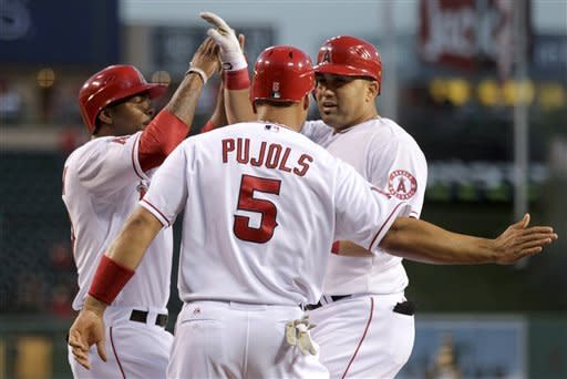 Los Angeles Angels' Kendrys Morales, right, celebrates his three-run home run with Howard Kendrick, left, and Albert Pujols during the first inning against the Oakland Athletics in a baseball game in Anaheim, Calif., Monday, April 16, 2012. (AP Photo/Chris Carlson)