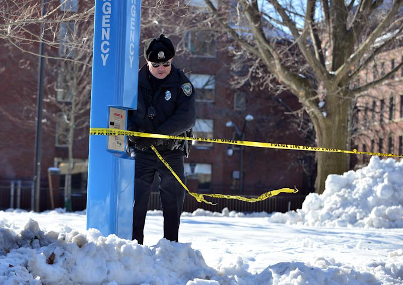 A police officer ties tape to secure an area at Harvard University in Cambridge, Mass., Monday, Dec. 16, 2013. Four buildings on campus were evacuated after campus police received an unconfirmed report that explosives may have been placed inside, interrupting final exams. (AP Photo/Josh Reynolds)