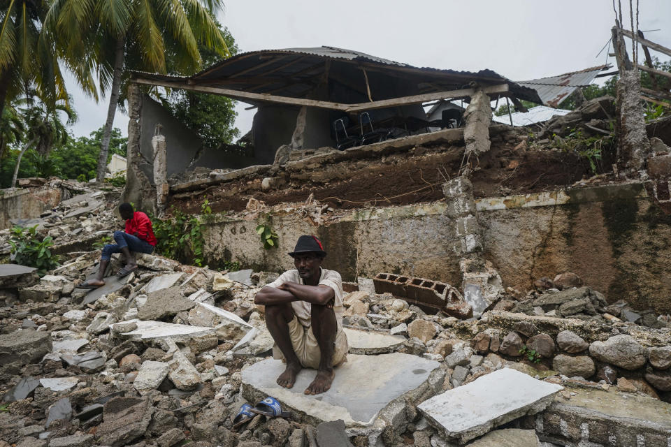 FILE - In this Aug. 17, 2021 file photo, a man crouches on the rubble of the hospital destroyed by the earthquake in Fleurant, Haiti, three days after the 7.2-magnitude quake hit the Caribbean nation. Twin tragedies on opposite sides of the world are piling misery on people that have seen far more than their share. In Haiti, yet another earthquake and yet another storm struck a country exceptionally ill-equipped to handle either.(AP Photo/Fernando Llano)