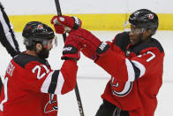 New Jersey Devils right wing Kyle Palmieri (21) congratulates right wing Wayne Simmonds (17) after Simmonds scored a goal during the third period of an NHL hockey game against the Detroit Red Wings, Thursday, Feb. 13, 2020, in Newark, N.J. (AP Photo/Kathy Willens)