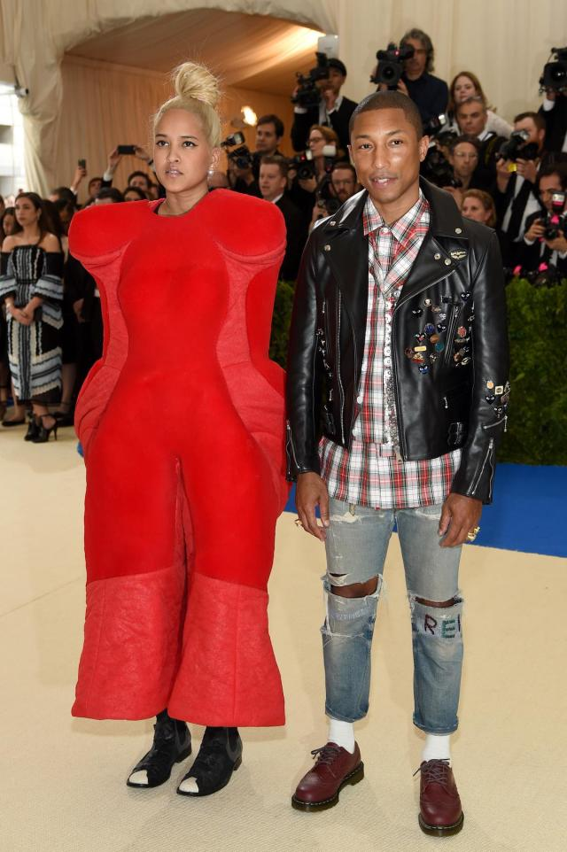 <p>Co-chair of the 2017 Met Gala, singer Pharrell was on theme in Comme des Garçons jeans, a plaid flannel, and a studded leather jacket. His wife, Helen Lasichanh, opted for a red Comme des Garçons look from Rei Kawakubo's Fall 2017 collection. (Photo by Jamie McCarthy/FilmMagic) </p>