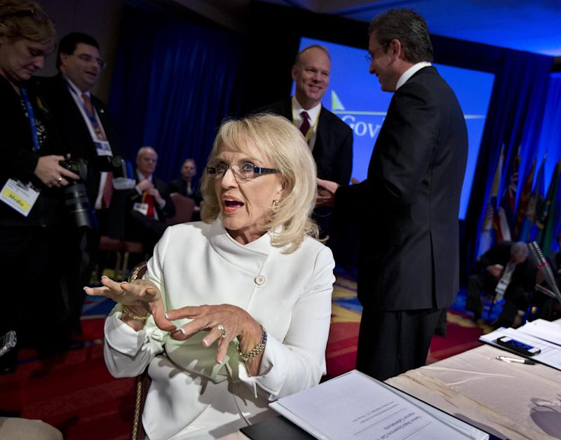 "Arizona Gov. Jan Brewer, left, gestures asIshe speaks to a reporter before the start of a Health and Homeland Security Committee meeting on ""Protecting Our Nation: States and Cybersecurity"" during the National Governors Association 2013 Winter Meeting in Washington, Saturday, Feb. 23, 2013. Standing at the back right, is Governor of Puerto Rico Alejandro García Padilla. Washington's protracted budget stalemate could seriously undermine the economy and stall gains made since the recession, exasperated governors said Saturday as they try to gauge the fallout from impending federal spending cuts. And both Democrat and Republican CEOs expressed pessimism that both sides could find a way to avoid the massive, automatic spending cuts set to begin March 1.   (AP Photo/Manuel Balce Ceneta)"