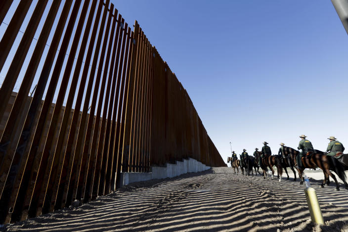 FILE - In this Oct. 26, 2018, file photo, mounted Border Patrol agents ride along a newly fortified border wall structure in Calexico, Calif. President Donald Trump is visiting Calexico on Friday, April 5, 2019, to tour the recently-built portion of the border fence that bears a silver plaque with his name on it. (AP Photo/Gregory Bull, File)