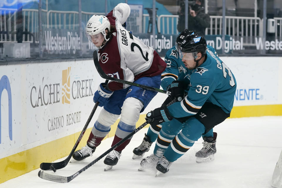Colorado Avalanche defenseman Ryan Graves (27) skates against San Jose Sharks center Logan Couture (39) and right wing Kevin Labanc during the first period of an NHL hockey game in San Jose, Calif., Wednesday, March 3, 2021. (AP Photo/Jeff Chiu)