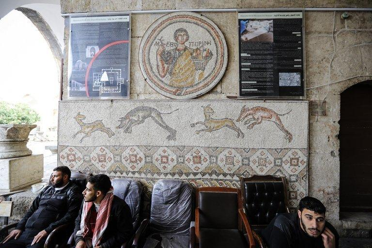 Syrian rebel fighters sit below Roman-era mosaics at the Alma Arra museum in Maaret Al-Numan on November 17, 2012