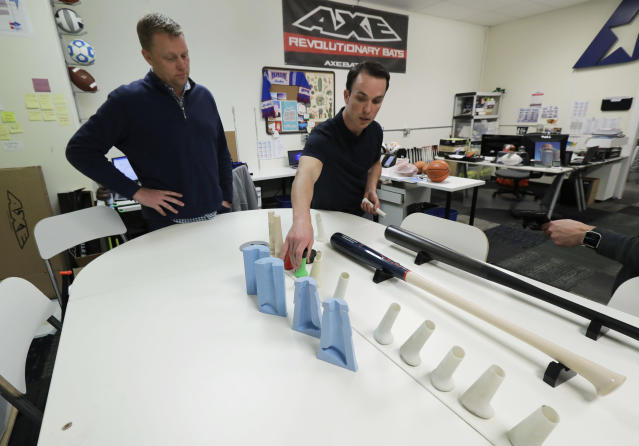 In this Feb. 8, 2018, photo, Brent Weidenbach, right, director of product management for Axe Bat, and Jay Helmick, senior vice president, stand near a table with some of the molds used to make prototype baseball bat handles at the company's headquarters in Renton, Wash. Axe Bat is trying to revolutionize baseball with a simple concept -- a bat handle that is shaped like the handle of an axe. (AP Photo/Ted S. Warren)
